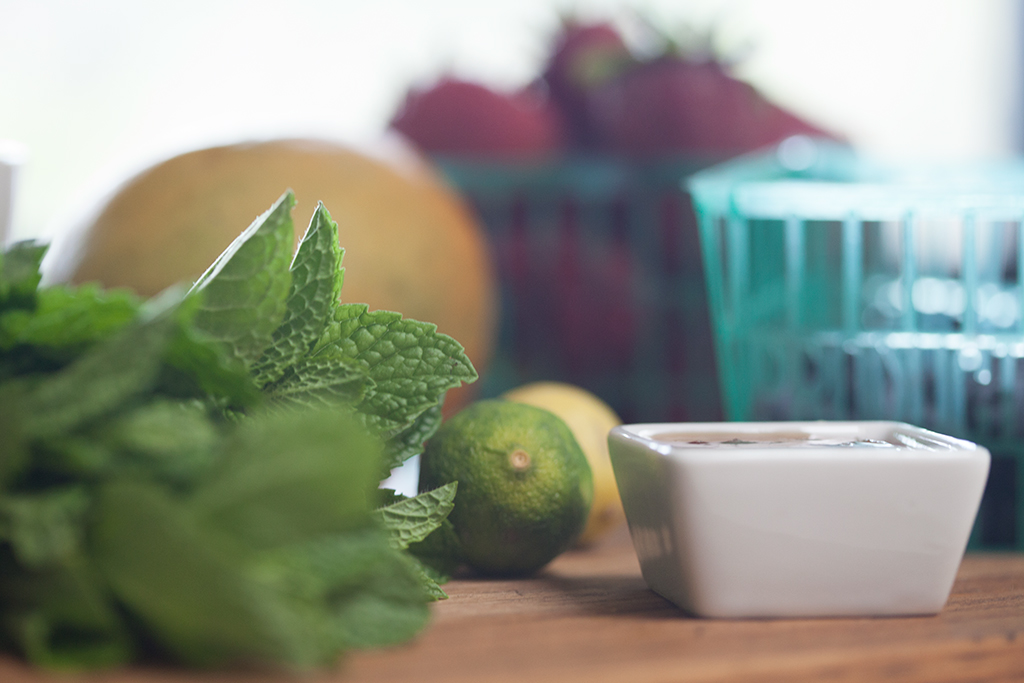 Fresh produce on wood countertop - mint, lime, mango and strawberries