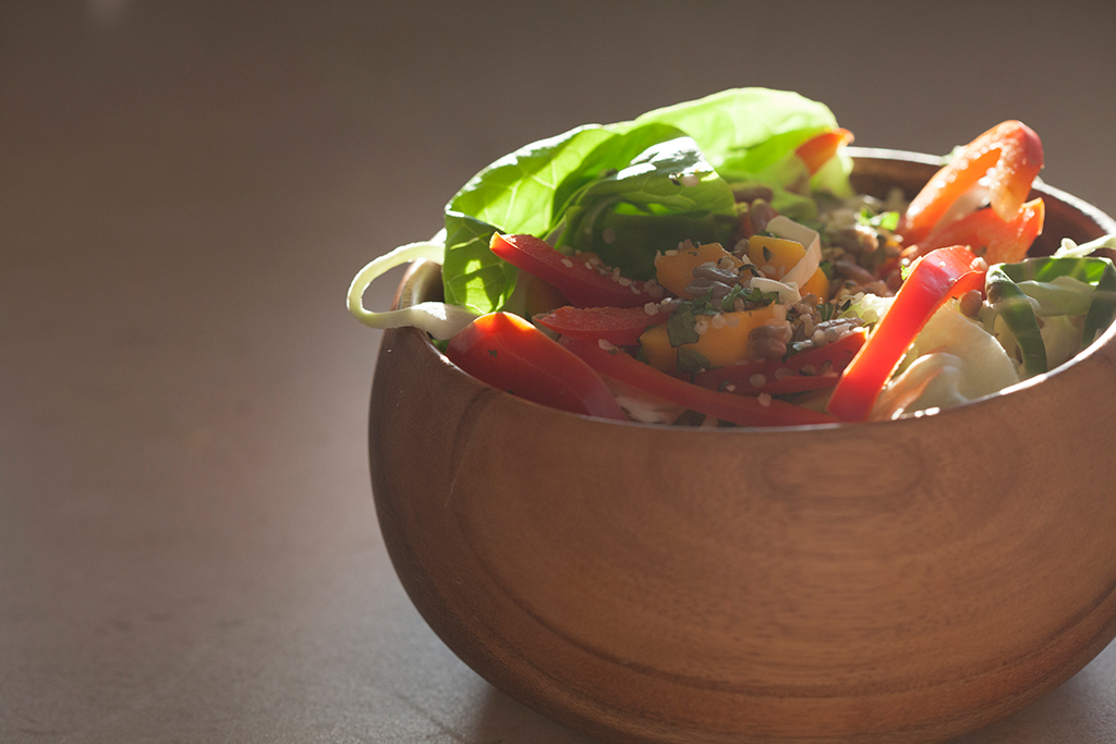 Mango and red pepper salad in wooden bowl