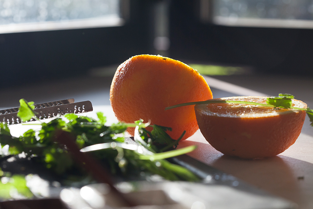Oranges and cilantro with zester on counter in sunlight