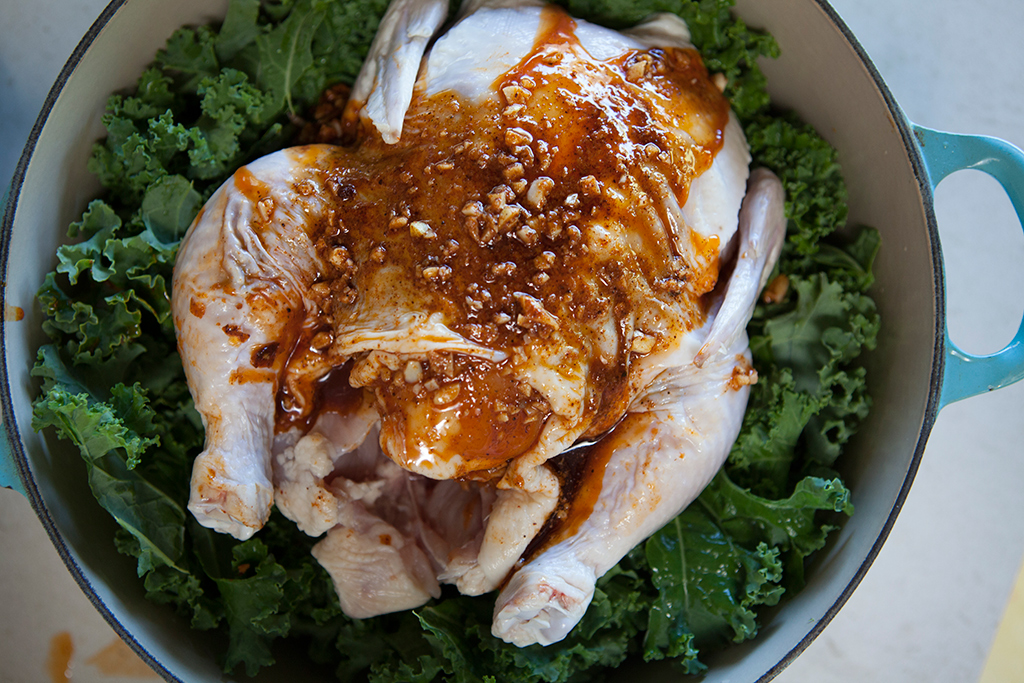 Chicken and kale with glaze on top ready to cook in cast iron pot