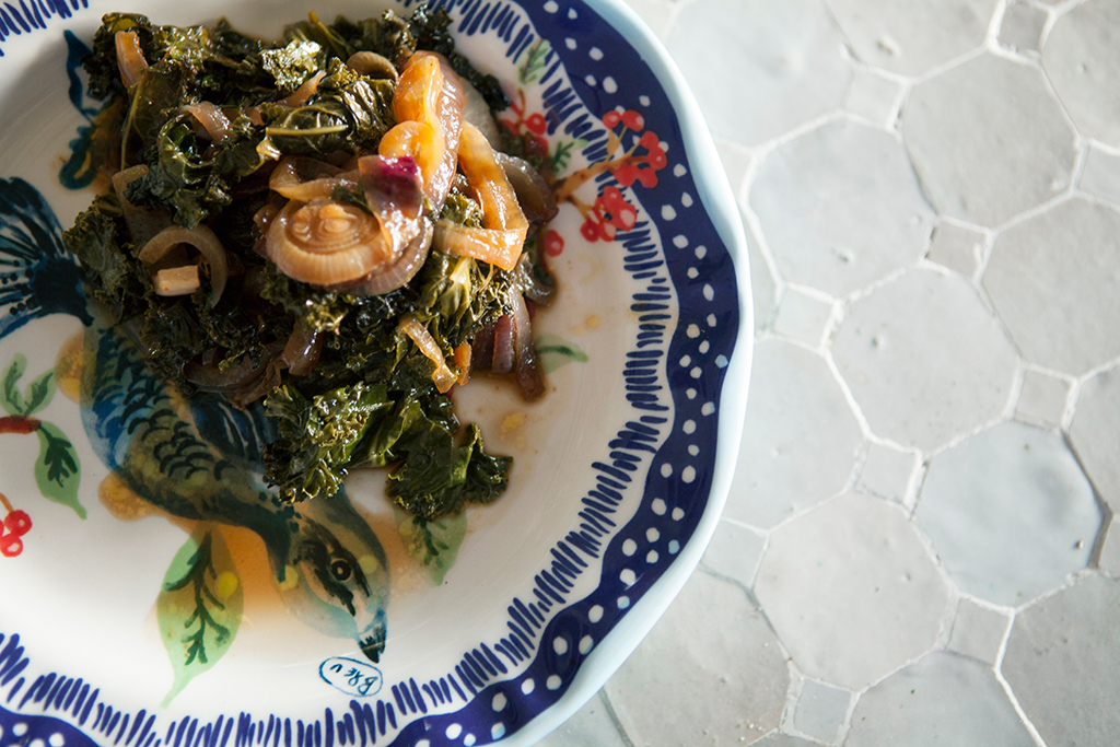 Kale and onions cooked and ready to eat on cute plate